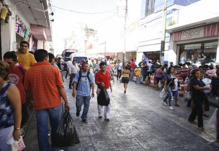 Comerciantes aseguran que ya no pueden absorver el cambio de precio del dólar y comenzarán a subir los precios de sus productos y servicios. Imagen de compradores en el centro histórico de Mérida. (Archivo/SIPSE)