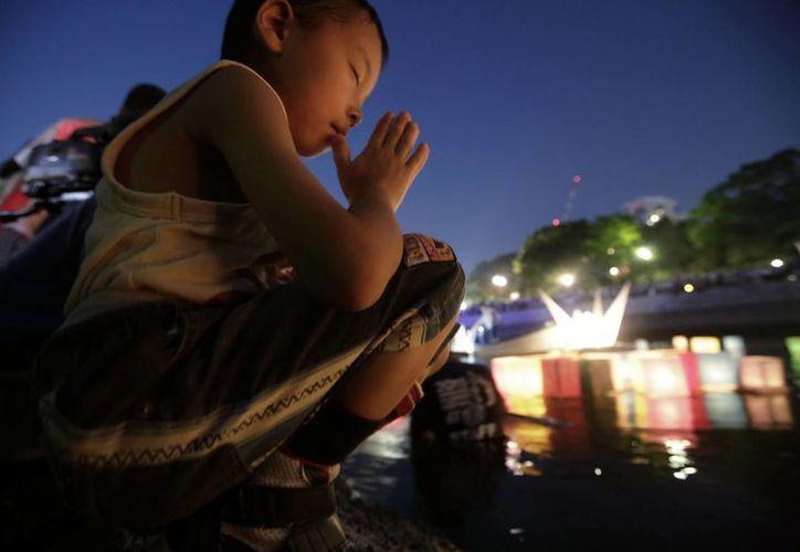 Un niño ofrece una oración después de lanzar una linterna de papel en el río Motoyasu donde cientos de miles de víctimas del bombardeo atómico murieron. (Agencias)