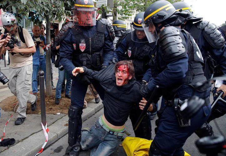 Una manifestante herido es evacuado por policías antimotines tras refriegas entre protestantes y la policía durante una protesta en contra de una ley laboral, este jueves 15 de septiembre del 2016 en París, Francia. (AP Foto/Christophe Ena)