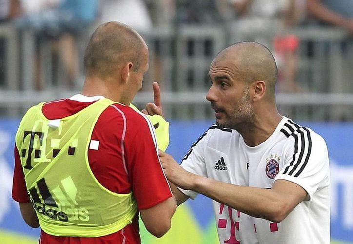El volante holandés Arjen Robben (i) dialoga con Pep Guardiola (d), durante un entrenamiento del Bayern. (EFE/Archivo)
