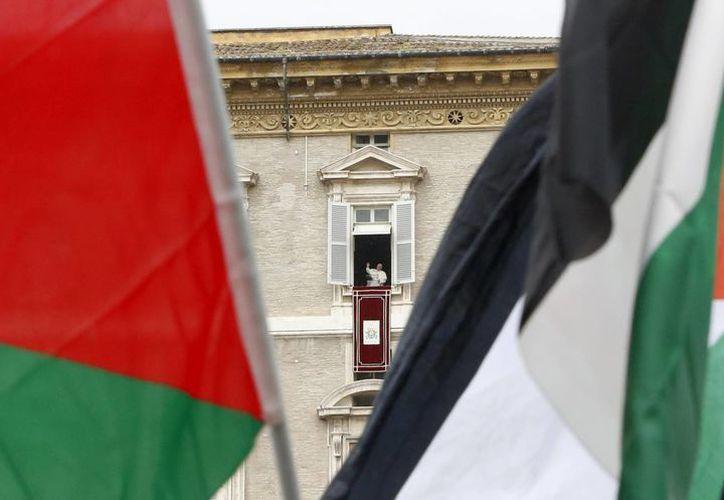 Banderas palestinas enmarca al Papa Francisco en el Angelus que realizó desde la ventana que da a la Plaza de San Pedro. (Foto: AP)