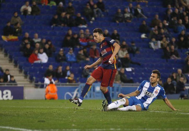 Munir El Haddadi al momento de eludir a Joan Jordan y anotar uno de los dos goles que hizo hoy para el Barcelona en su victoria sobre Espanyol para calificar a la ronda de los ocho mejores en la Copa del Rey. (AP)