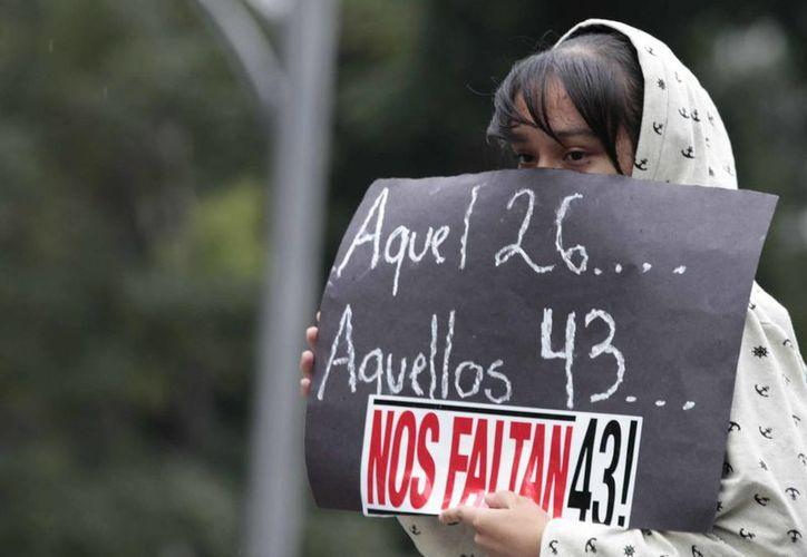 La Segob dijo que la búsqueda de los normalistas de Ayotzinapa ha sido un trabajo intenso. Imagen de una joven que sostiene un cartel durante una protesta en relación a los 43 estudiantes desaparecidos. (Archivo/Notimex)