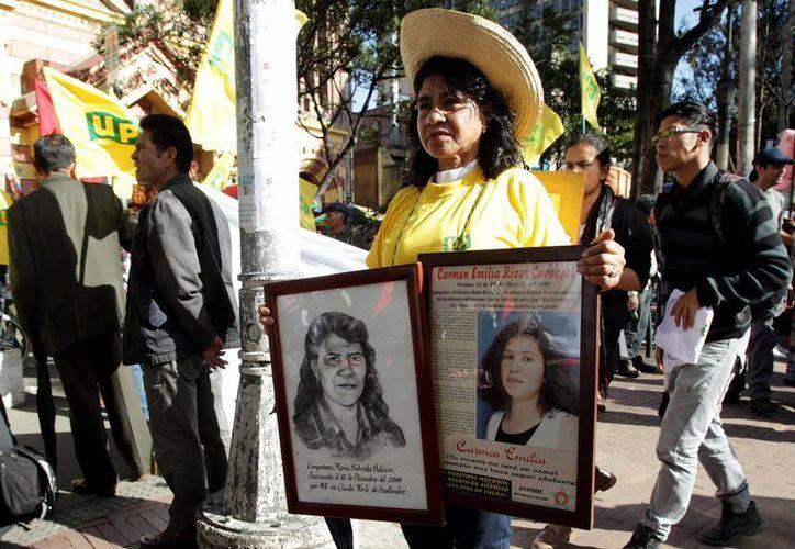 Imagen de archivo de una mujer con fotografías de víctimas del conflicto participa en una marcha por el Día Nacional de la Memoria y Solidaridad con las Víctimas, en Bogotá, Colombia. (EFE/Archivo)
