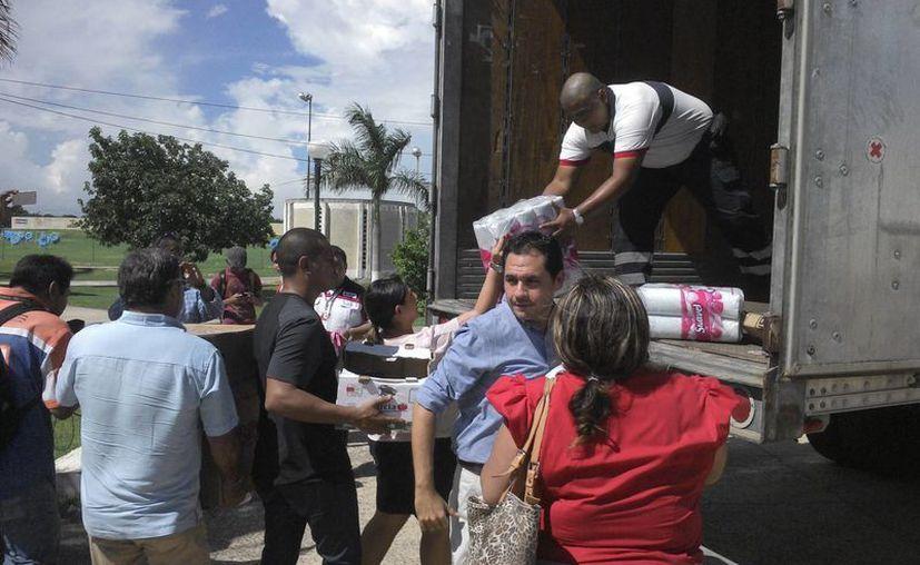 Los regidores priistas entregan ayuda en el evento de Grupo SIPSE. (Cortesía)