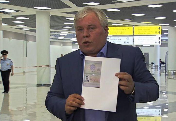 Anatoly Kucherena, abogado de Snowden, muestra un documento que permitee el ingreso del experto informático en territorio ruso. (Agencias)