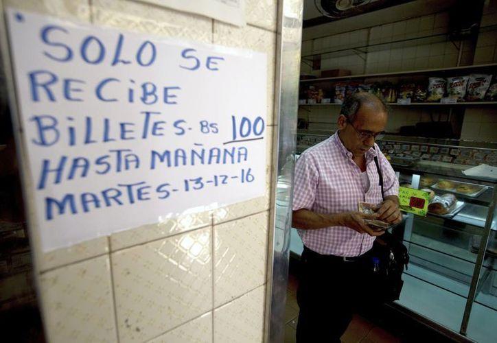 Un hombre en Venezuela cuenta su dinero al lado de un letrero de una tienda que informa que hasta el martes podrá recibir biletes de 100 bolívares. (AP)