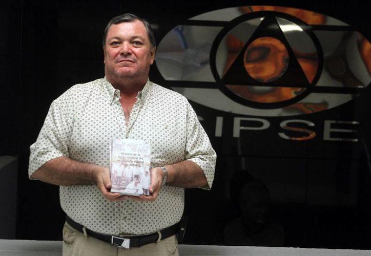 El profesor Alejandro de Jesús Castro Escalante posa con un ejemplar de su libro 'Historia de la lucha sindical del magisterio estatal yucateco'. (César González/SIPSE)