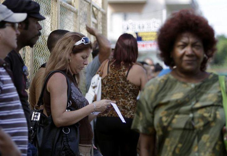Una mujer revisa el formulario para solicitar un pasaporte en La Habana. (Agencias)