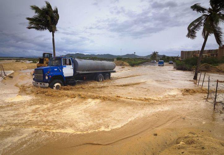 Un vehículo transita por una vía inundada este domingo, tras el paso del huracán Odile en Los Cabos en el estado de Baja California, México. (EFE)