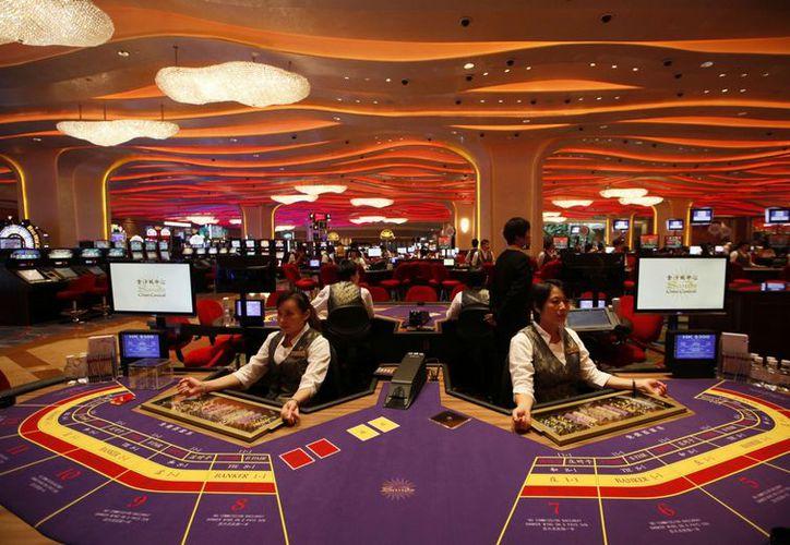 Crupieres en una mesa de bacará en un casino en Macao, en el sur de China, durante la inauguración del Sheraton Macao Hotel. (Agencias)