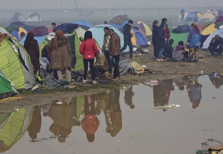 Los migrantes se reúnen alrededor del fuego en una estación de frontera griega.  La ONU asegura que la mayoría de quienes emprendieron viaje en las barcazas hacia Europa son mujeres y niños. (Foto AP / Visar Kryeziu)