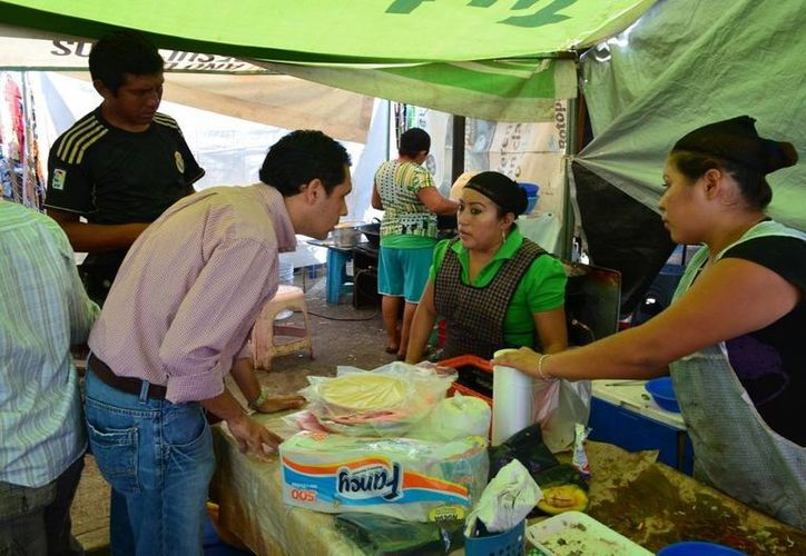 El regidor priista Rubén Segura Pérez platica con una vendedora del tianguis de San Roque. (SIPSE)