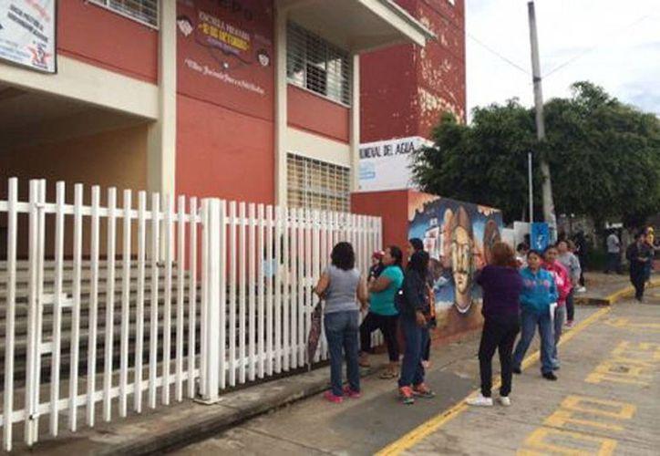 Las escuelas pertenecientes a la CNTE abrieron los planteles desde temprana hora. Imagen de un grupo de padres de familia en las puertas de un colegio. (Óscar Rodríguez/Milenio)