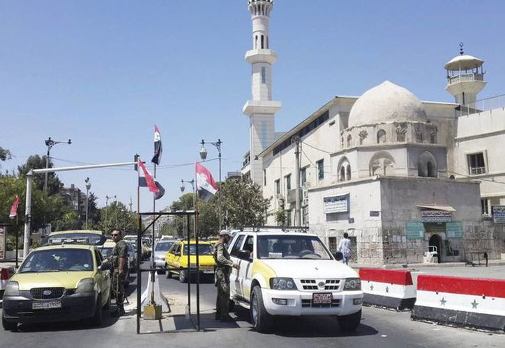 Soldados sirios revisan la identidad de conductores en un punto de control en Damasco. (EFE/Archivo)
