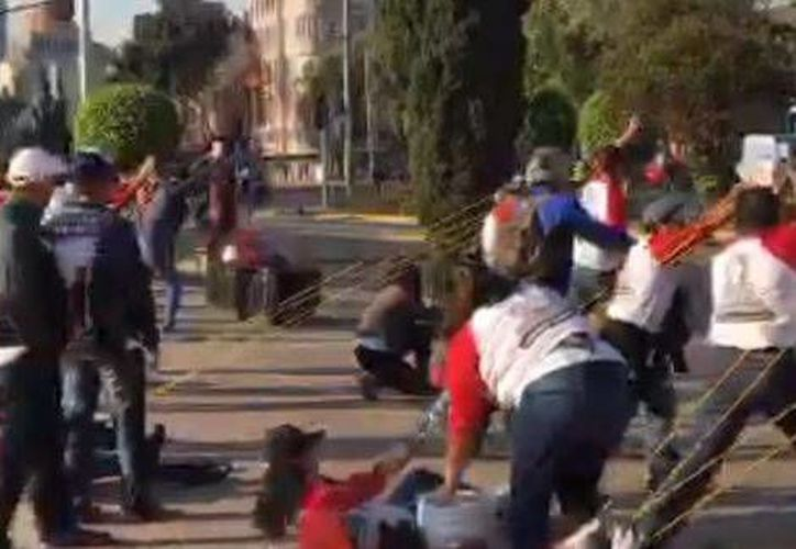 Los manifestantes lanzan pañales hacia las instalaciones del PRI nacional con una resortera. (Captura de pantalla)