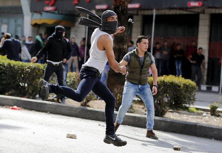 Manifestantes palestinos lanzan piedras contra soldados israelíes durante enfrentamientos en la ciudad cisjordana de Hebrón. (EFE)