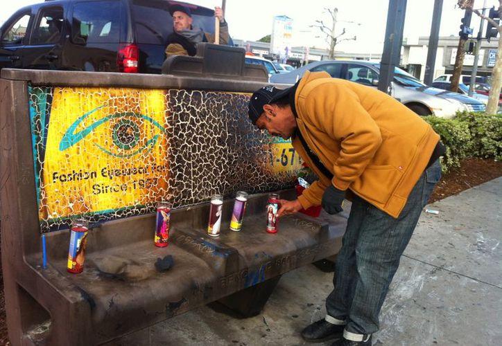 Phil Furtado coloca una vela en el sitio donde una indigente de 67 años fue atacada. (Agencias)