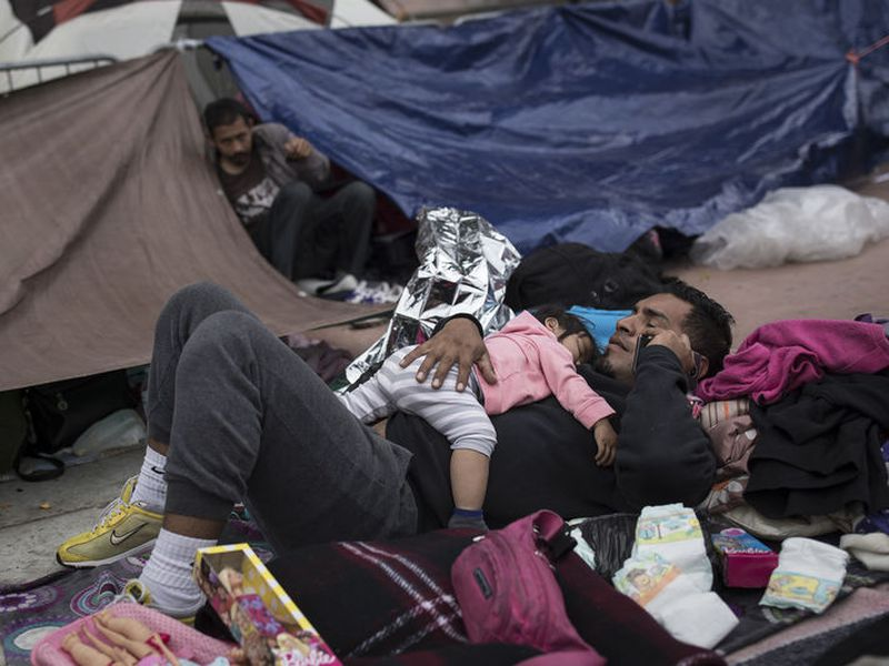 A migrant father and child, who traveled with the annual caravan of Central American migrants, rest where they set up camp to wait for access to request asylum in the US.