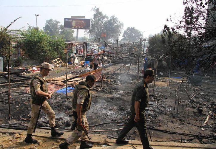 Personal del Ejército de Egipto camina entre los restos materiales de una protesta a favor de Morsi en Nasr, El Cairo. (Agencias)