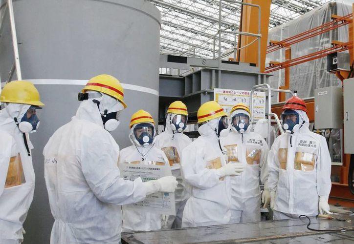 El primer ministro nipón, Shinzo Abe (d), visita la accidentada planta nuclear de Fukushima, en Japón. (Archivo/EFE)