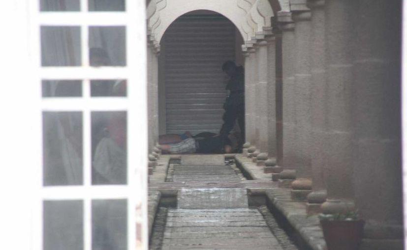 Policías custodian a presuntos asaltantes detenidos en un complejo de departamentos. (Julián Miranda / SIPSE)