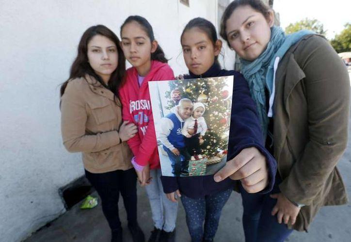 Brenda Avelica, de 24 años, junto a sus hermanas menores, Joselyn, de 19, Fatima de 13, y Yuleni, de 12, muestran una foto de su padre. (Foto tomada de laopinion.com)