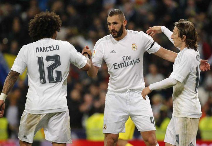 El delantero del Real Madrid Benzemá (c) es felicitado por Marcelo (i) y Modric tras marcar ante el Villarreal, durante el partido de Liga de Primera División que se disputó en el estadio Santiago Bernabéu, en Madrid. (EFE)
