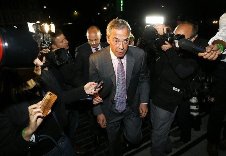 Nigel Farage, líder del antieuropeo Partido de la Independencia de Reino Unido (UKIP por sus siglas en inglés), es rodeado por la prensa cuando llega para escuchar los resultados de las elecciones al Parlamento Europeo en Guildhall, Southampton, Inglaterra. (AP)