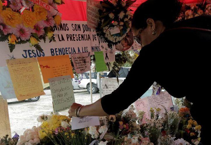 Una mujer observa un altar erigido en el lugar donde fallecieron el pasado 18 de mayo 33 niños de Fundación, Colombia. (EFE)