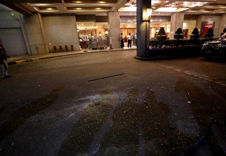 Fotografía donde se ve reflejada la sombra de trabajadores que limpian los restos de vidrios, después de una explosión. (EFE)