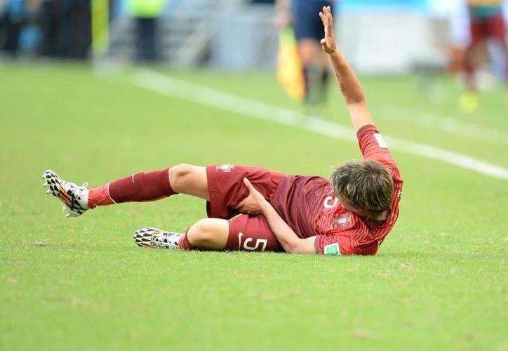 Coentrao abandonó el estadio Fonte Nova de Salvador en camilla, en partido en que Alemania goleó a Portugal. (EFE)