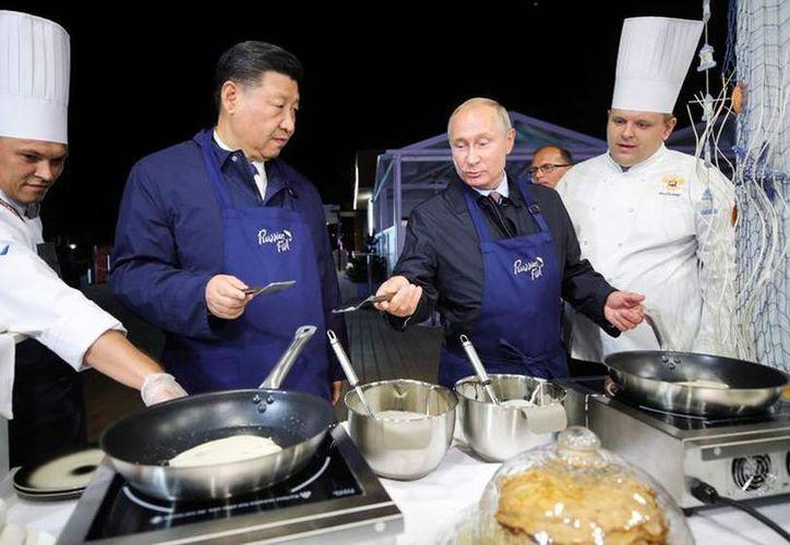Los presidentes de Rusia y China, Vladimir Putin y Xi Jinping compartieron un momento juntos en la cocina. (AFP)