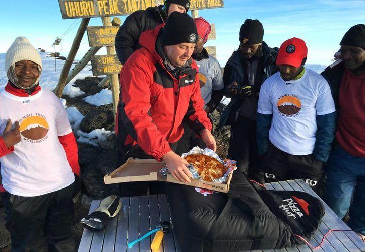 El gerente general de Pizza Hut África, Randall Blackford, centro, celebró el récord mundial de la organización Guinness World Records por la entrega más elevada de una pizza en el monte Kilimanjaro en Tanzania. (Consea Dissa/Pizza Hut vía AP)