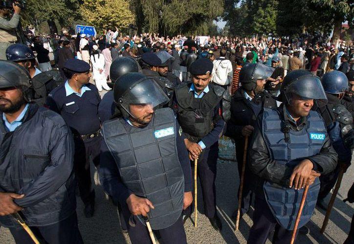 Policía de Pakistán resguardan a participantes de una festividad religiosa, quienes mostraron su apoyo y solidaridad a los familiares de las víctimas del ataque contra un escuela, en el que murieron más de 140 personas, la mayoría niños. (AP)