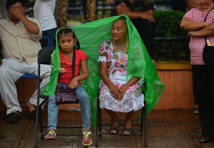 Algunas familias precavidas salieron a pasear llevando con que cubrirse del agua. (Luis Pérez/SIPSE)
