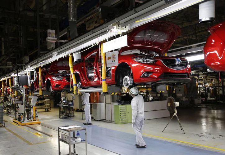 Obreros de una planta de Hofu, Japón, trabajan en el ensamblaje del Mazda6. (Agencias)
