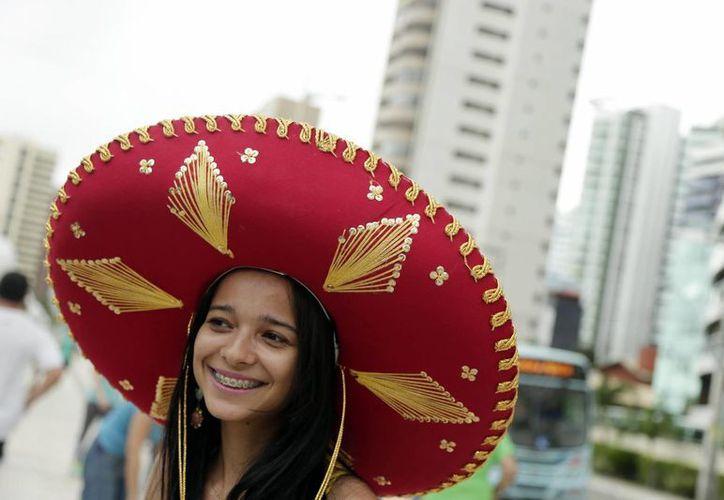 Pese a la intensa rivalidad deportiva entre México y Brasil, también hay amor mutuo, como se demuestra en esta foto, con una brasileña con un sombrero de charro mexicano en Fortaleza. (Foto: AP)
