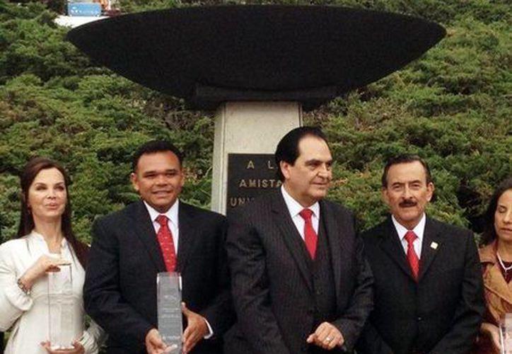 """El gobernador Rolando Zapata (i) con el premio """"Clares"""". (Milenio Novedades)"""