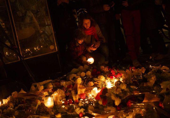 Una madre y su hijo encienden velas enfrente del restaurante The Belle Equipe, que fue uno de los sitios donde terroristas atacaron y mataron a civiles este viernes, en París.  (AP)