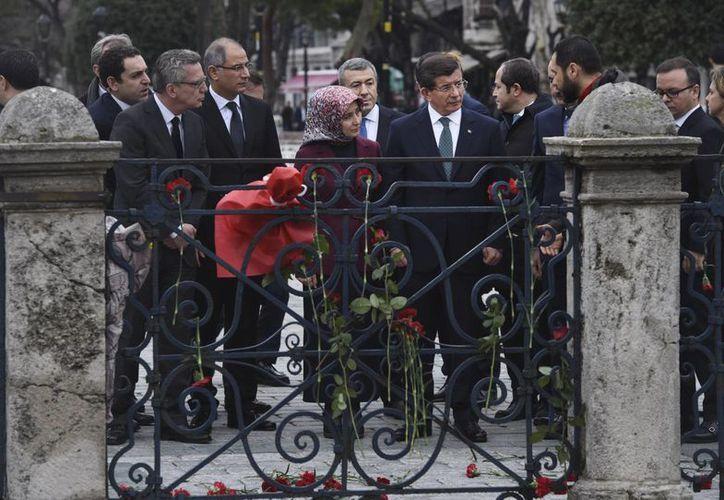 El primer ministro turco Ahmet Davutoglu (centro derecha) acompañado por su esposa Sare (centro) y el ministro del Interior alemán Thomas de Maiziere (izquierda),  mientras hablan con un policía al visitar, hoy miércoles, el sitio del atentado en el distrito Sultanahmet de Estambul. (Bulent Kilic, Pool Photo via AP)