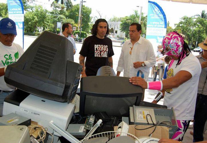 Luchadores de Triple A colaboraron en la recaudación de desperdicios electrónicos, que ayer arrancó con buena respuesta de la ciudadanía. (Wilbert Argüelles/SIPSE)