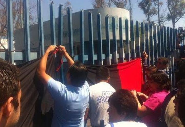 Al mediodía los huelguistas integrantes del Steuaq colocaron las banderas rojinegras en la puerta principal de la UAQ. (Milenio)