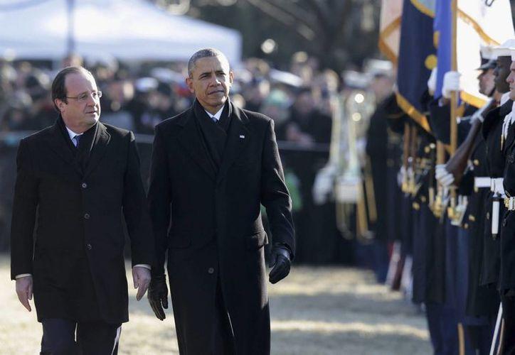 El presidente estadounidense Barack Obama y su homólogo francés François Hollande (izquierda) pasan revista a una guardia de honor durante la ceremonia de bienvenida en la Casa Blanca, en Washington, E.U. (EFE)