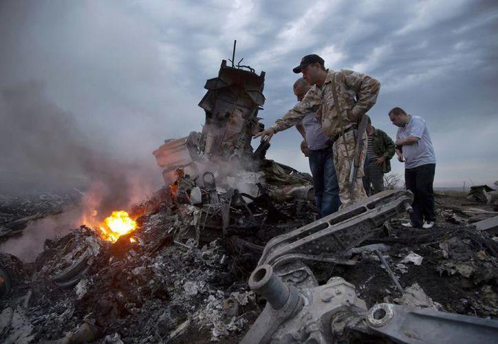 El presidente de Ucrania, Pietro Poroshenko, aseguró que la caída del avión es un acto terrorista; en tanto, rebeldes aseguraron haber encontrado la caja negra de la aeronave. (AP)