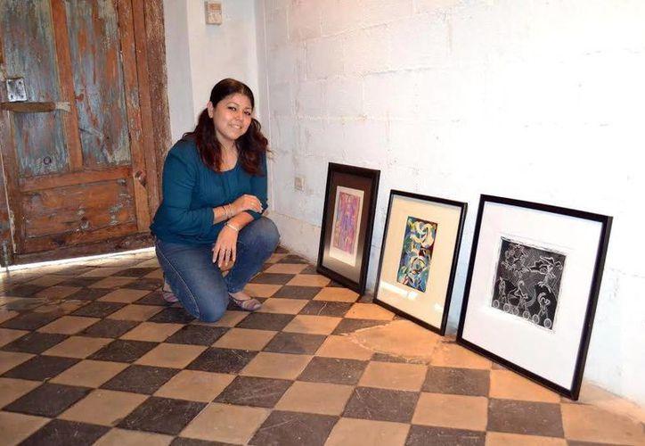 Nayeli González posa con parte de sus grabados que se encuentran en exposición. (Milenio Novedades)