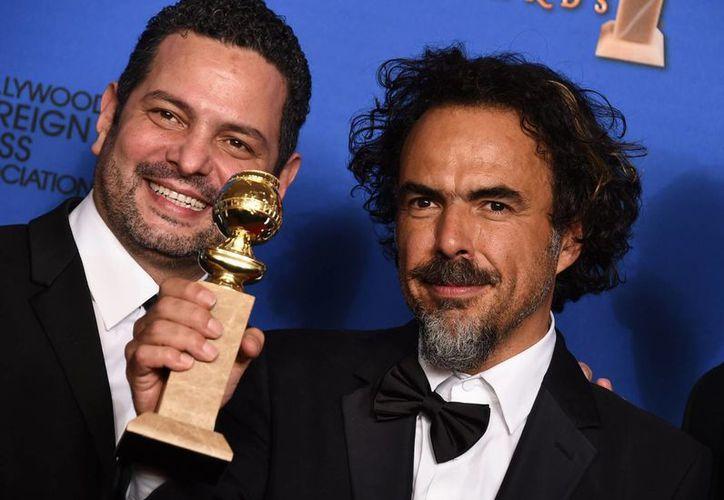 El director mexicano Alejandro González Iñárritu con el Globo de Oro que obtuvo la película Birdman por Mejor Guion. (AP)