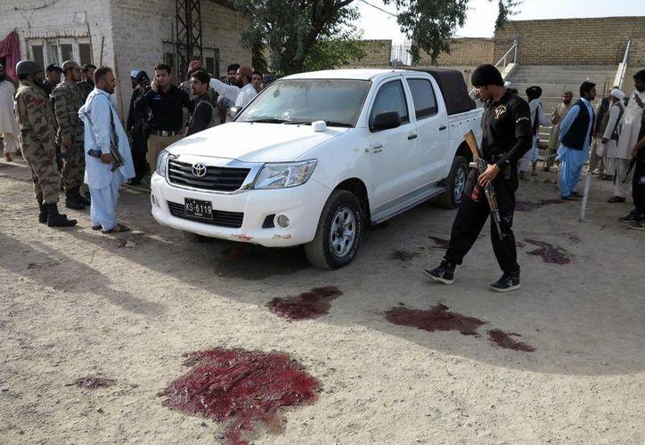 Oficiales de seguridad paquistaníes revisan la escena donde desconocidos abrieron fuego hoy contra un grupo de pastores. (EFE)