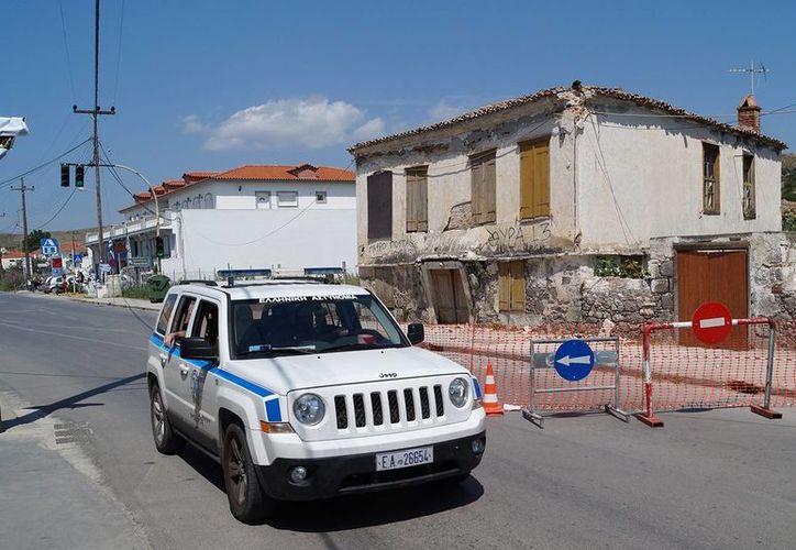 Una patrullas de policía pasa por un edificio antiguo que se dañó después del terremoto. (Agencias)