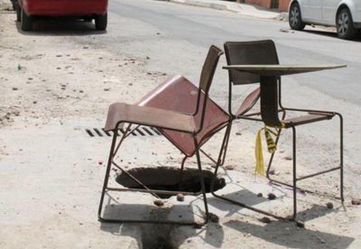 Colonos y maestros colocaron sillas encima para evitar caídas en la coladera. (Rossy López/SIPSE)
